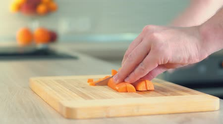 A man cuts vegetables on the board. Close-up