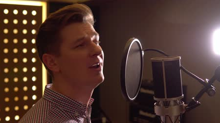 Man sings in recording studio. Face close up