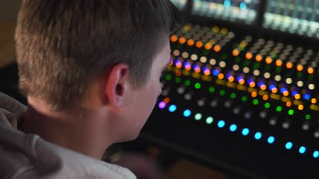 A man works in a recording studio on a mixing console. Wideo