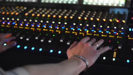 A man works in a recording studio on a mixing console. Hands close up Wideo