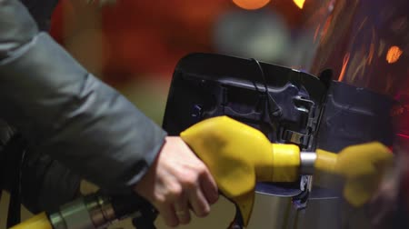 Woman fills gasoline car. Hand close up