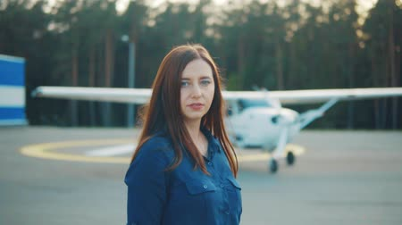 фон : A young woman stands on the background of a light aircraft