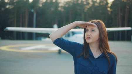 фон : Young woman looks into the sky against the background of a private plane