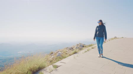 overcome : A girl walks along a path on top of a mountain.