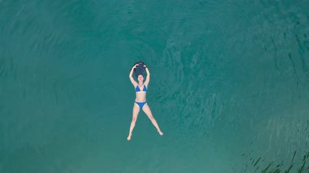 plavec : Drone view of a woman in a swimsuit lying on her back and swims in the blue Lake