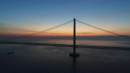 akashi strait : Aerial Akashi Kaikyo Bridge in the morning glow tower main cable pan Stock Footage