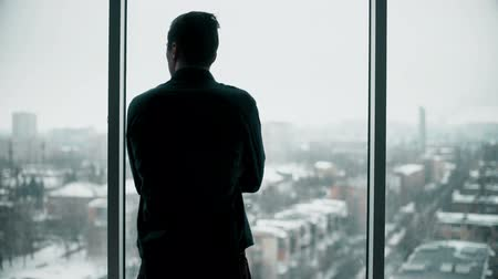 trabalhar fora : Middle aged businessman looking out a bright office window and thinking