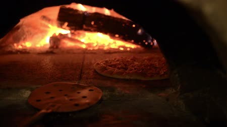 készítő : cooking a pizza in a wood fired oven