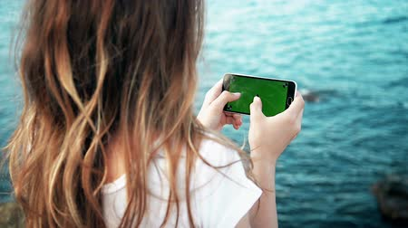 phablet : Young Girl is Holding Smartphone with Green Screen at Evening Time Sea Stock Footage