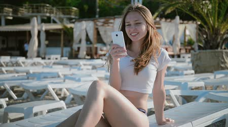 napágy : Young woman using cellphone while lying on sunbed on beach Stock mozgókép