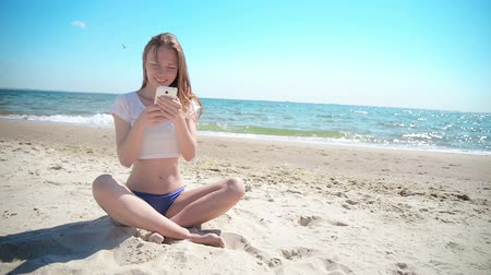 ilk : Girl with mobile phone sitting on sand near sea and blue sky. First love.