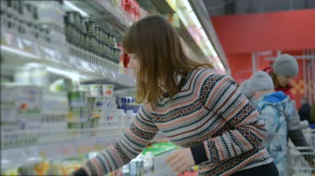 recados : Young woman chooses dairy produce in the store Stock Footage