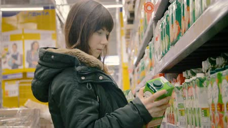 consumismo : Woman chooses juice in the supermarket