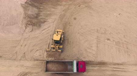 drone : Aerial view of bulldozer pouring sand into truck Stock Footage