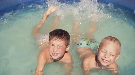 len : two boys  close-up floating in the pool, 1080p