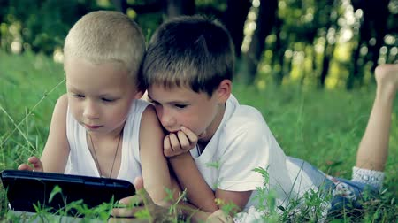 small park : children close up in  the park playing on a tablet  HD