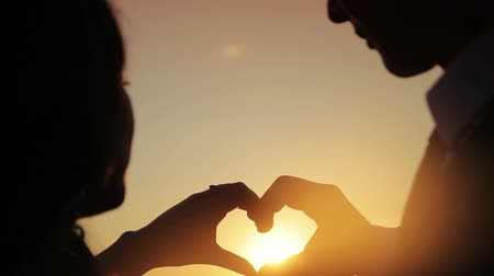 Hands of men and women came together form the symbol of a heart shape at sunset,  love and tenderness continuation of humanity Stock Footage