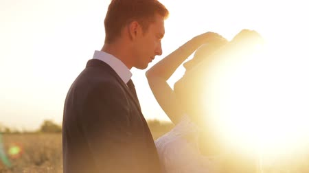 sylwetka : Young couple in love bride and groom on the background of sunset, straightens hair backlight, field of wheat, soft and romantic, white dress, tie, nature, video 1080p Wideo