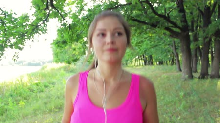 musculação : The young beautiful girl is engaged in sports. Female runner jogging during outdoor workout in the park. Fitness model outdoors.  Weight loss. Listen to music