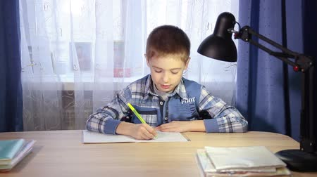 aritmética : child doing homework, writing in a notebook in the evening at the  table