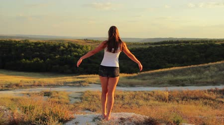 vida : Young beautiful girl standing on a mountain at sunset hands raised  desire to fly Vídeos