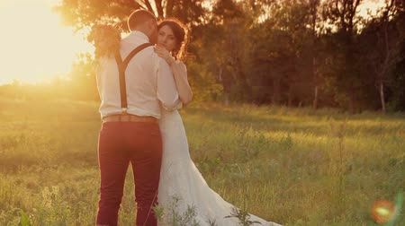 nevěsta : Young beautiful couple bride and groom on their wedding day walking outdoors on a spring character. Wedding couple, happy newlywed woman and man embracing in a green park  at sunset Dostupné videozáznamy