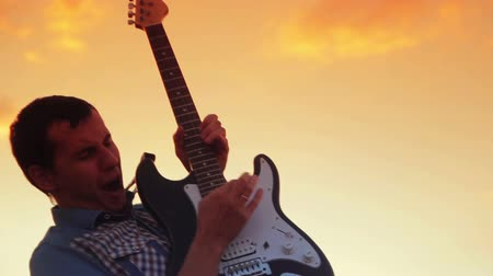 gitáros : Male guitarist playing rock in the sunset on a warm summer  night Stock mozgókép