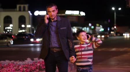 сообщить : man and child go through the city night and talking on a smartphone on the background  of night lights