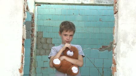 unicef : dirty little orphan boy standing with a soft toy and pats her on the background of the ruins of the destroyed  houses