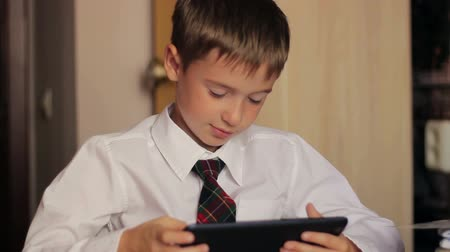érintés : boy in a white shirt and tie sat at his desk and writes on the tablet communicates with  friends