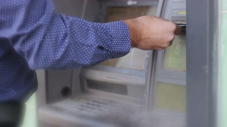 mevduat : Detail of human hand insertion and removal of a credit card in an old  dirty and dangerous ATM. the mans hand