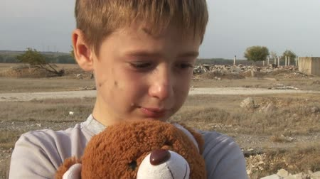 unicef : dirty little orphan boy close-up crying and petting a stuffed toy wipes the tears on the background of the ruins of the  destroyed houses