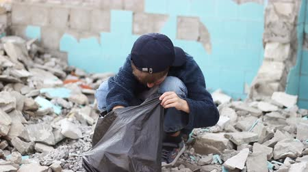evsiz : homeless orphan boy looking for food in the package among the ruins of  houses
