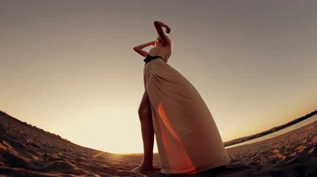 haj : Young seductive woman with long hair in a nice dress standing on the beach at  sunset