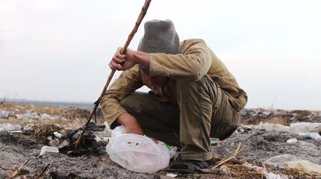 csavargó : dirty homeless man sits on a close-up of the trash and eat the bread of a video package on the  move