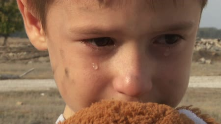 unicef : dirty little orphan boy close-up crying and petting a stuffed toy on the background of the ruins of the destroyed  houses Stock Footage