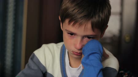 cover : little boy sitting at a desk  crying, tears on his face
