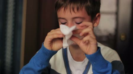 tosse : Sick boy blowing his nose into a napkin while sitting at a table at  home