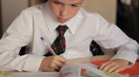 vizyon : Little boy close-up of a schoolboy in a white shirt and tie doing homework sitting at a table and writes in a notebook pen Stok Video