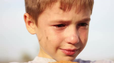 perdido : dirty orphan boy close-up crying and looking at camera on the background of the  ruins