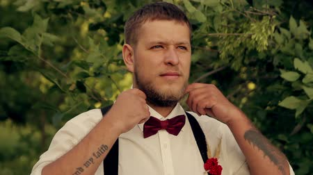 формальный : groom wears a tie in  the park at sunset
