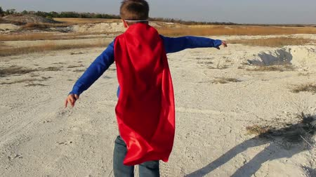 acreditar : superhero boy runs through the mountains and trying to fly
