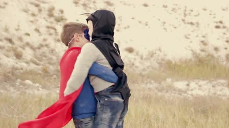 acreditar : Two boys dressed as superheroes playing in the park outdoors