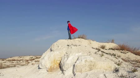 fantazja : superhero  boy runs through the mountains and trying to fly