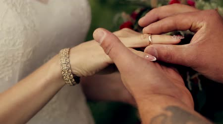 halkalar : groom puts the ring on bride finger at  sunset in the park Stok Video