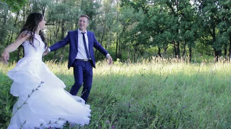 подвенечное платье : happy bride and groom are dancing in park in their wedding day. first wedding dance of beautiful young couple. weddings. green nature background. people in love. woman and man smiling  and dancing
