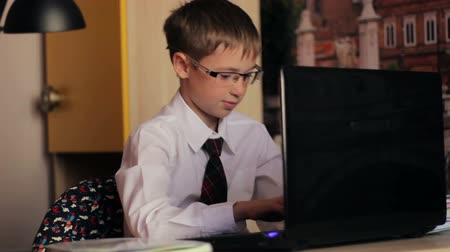 kablosuz teknoloji : A boy with glasses, a white shirt and tie, working on laptop computer. The young man knows how to handle technology toys, the concept of education, training, Internet, homework and  social media