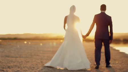 koca : the bride and groom are on the beach at sunset on the sand in the sun