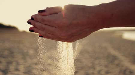 philosopher : Female hands sypyat sand at sunset in the sun