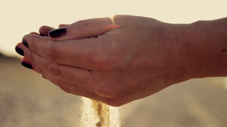 philosopher : Female hand scatter the sand at sunset